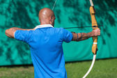 Archer at shooting range with bow and arrow — Stock Photo