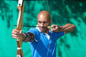 Archer aiming at target with bow and arrow — Stock Photo
