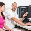 Radiologist councelling a patient using images from tomograpy or MRI — Stok fotoğraf #65915171