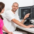 Radiologist councelling a patient using images from tomograpy or MRI — Stok fotoğraf #65915199