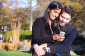 Couple in love looking at cellphone — Stock Photo