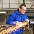 Steel construction worker grinding metal with angle grinder — Stock Photo #66299191