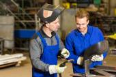 Instructor teaching trainee how to weld metal — Stock Photo