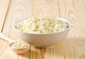 Cottage cheese in porcelain bowl with wooden spoon  — Stock fotografie