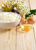 Cottage cheese and eggs on the meadow flowers background — Foto de Stock
