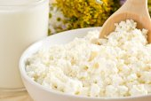 Cottage cheese in bowl with wooden spoon and milk — Stockfoto