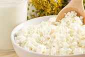 Cottage cheese in bowl with wooden spoon and milk — Stock Photo