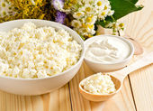 Cottage cheese in bowl with wooden spoon and sour cream — Stock Photo