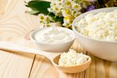 Cottage cheese in bowl with wooden spoon and sour cream — Stockfoto