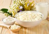 Cottage cheese in bowl with wooden spoon and sour cream — Foto de Stock