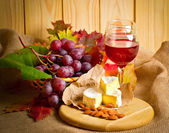 Red wine with cheese, almonds and grapes — Stock Photo