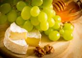 Still life of cheese, honey, walnuts and grapes — Stock Photo