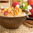 Oatmeal with apple and cinnamon in the bowl and cinnamon sticks — Stock Photo #73496583