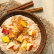 Oatmeal with apple and cinnamon in the bowl and cinnamon sticks — Stock Photo #73496607