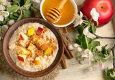 Oatmeal with apple, honey and cinnamon in the bowl and cinnamon — Stock Photo