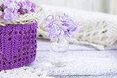 Lilac flowers in a small glass bottle — Stock Photo