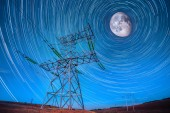 Electricity power poles on night sky and startails moon backgrou — Stok fotoğraf