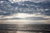 Sunset over the ocean on a cloudy day — Stok fotoğraf