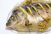 Carp cooked on a plate adorned with colorful — Stock Photo