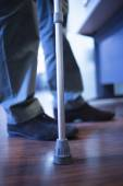 Man walking with crutches in hospital clinic — Stock Photo