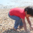 Young indian toddler boy kid playing in sand stone near the sea ocean beach shore. cute small child play near sea shore. — Stock Photo #52627799