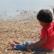 Young indian toddler boy kid playing in sand stone near the sea ocean beach shore. cute small child play near sea shore. — Stock Photo #52627835