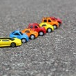 Miniature colorful cars standing in line on road sale concept. Different colored cars - blue, yellow, orange, white and red color cars standing next - car agent sale concept — Stock Photo #52628065