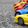Miniature colorful cars standing in line on road sale concept. Different colored cars - blue, yellow, orange, white and red color cars standing next - car agent sale concept — Stock Photo #52628563