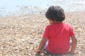 Young indian toddler boy kid playing in sand stone near the sea ocean beach shore. cute small child play near sea shore. — Stock Photo