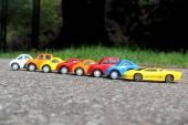 Minature colorful cars standing in line on road sale concept. Different colored cars - blue, yellow, orange, white and red color cars standing side by side on road next to grass — Stock Photo
