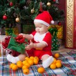 Baby in Santa costume near a Christmas tree — Stock Photo #55493819
