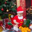 Baby in Santa costume near a Christmas tree — Stock Photo #55493987