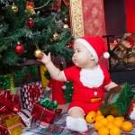 Baby in Santa costume near a Christmas tree — Stock Photo #55499507