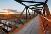 Foot bridge over railway at sunset — Stock Photo