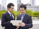 Asian businessmen using ipad — Stock Photo