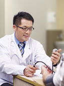 Doctor measuring blood pressure — Stock Photo