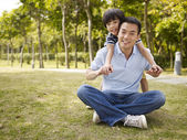 Asian father and son having fun in park — Stock Photo