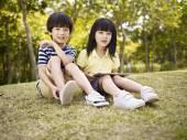 Beautiful asian children sitting on grass — Stock Photo