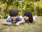 Asian children playing with magnifier outdoors — Stock Photo