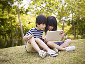 Two asian children using tablet outdoors — Stock Photo