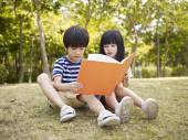 Asian children reading book outdoors — Stock Photo