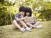 Два азиатских детей используя планшетные на открытом воздухе — Стоковое фото
