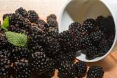 Blackberries in cup on a wooden table — Stock Photo