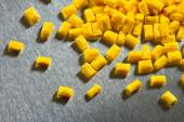 Yellow polymer pellets on stainless steel sheet — Stock Photo
