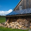 Solar power panels on barn roof with stacked fire wood — Stock Photo #71670293