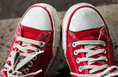 Feet in dirty red sneakers and jeans outdoors. — Stockfoto