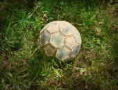 Grunge football or soccer ball on a green lawn — Stock Photo