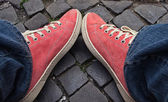 Feet in red sneakers and jeans outdoors. — Stock Photo