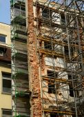Reconstruction of old building with scaffolding undergoing repai — Stock Photo