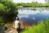 The boy catches fish in the river on a self made rod — Stock Photo